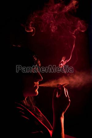 illuminated profile of woman smoking