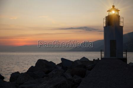 lighthouse shining over rocky beach