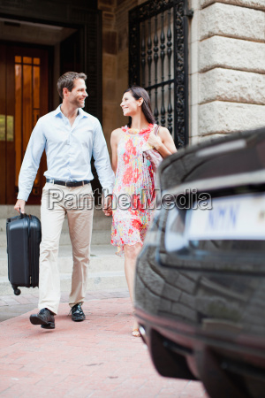 couple walking to car on city