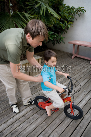 boy riding a bike with father