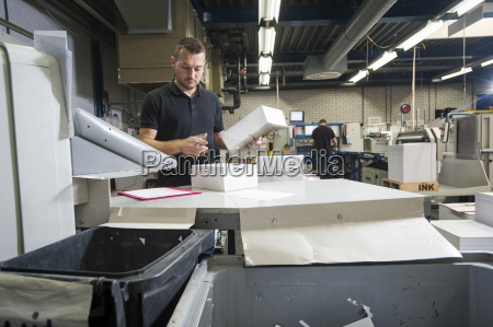 worker preparing paper for machine in