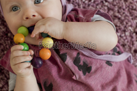 baby girl with teething toy