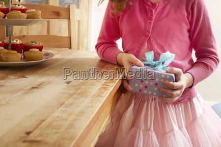 girl holding birthday present mid section