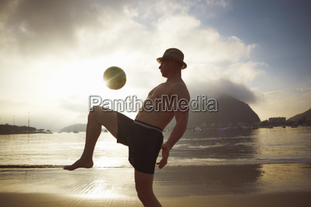 mid adult man playing keepy uppy