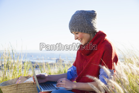 young woman using laptop whilst sitting