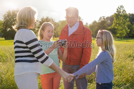 girl holding camera with grandparents and