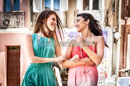 two fashionable young women chatting and