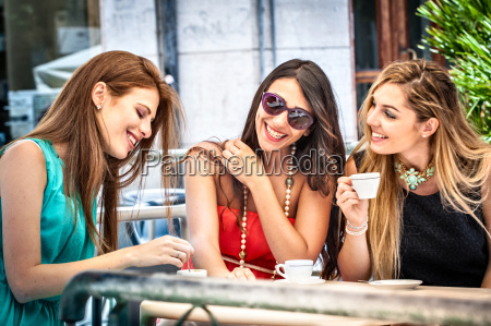 three young female friends drinking espresso