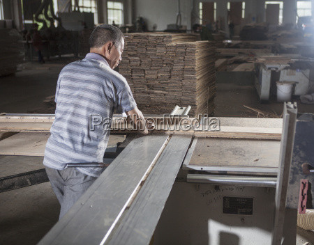 carpenter working on wood plank in