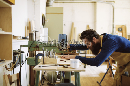 mid adult craftsman using machine in