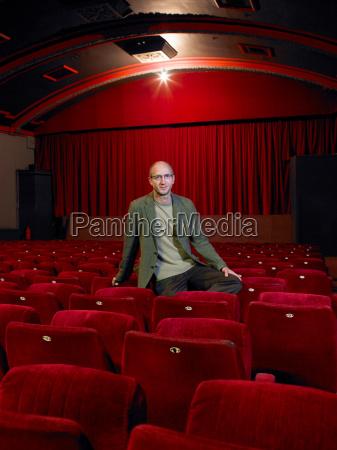 mature man sitting in empty cinema