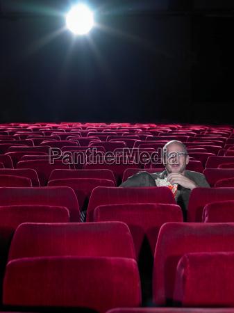 mature man eating popcorn in cinema