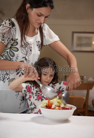 woman helping daughter to toss salad