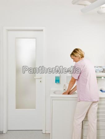 female dentist washing her hands