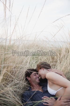 couple lying in reed laughing