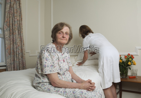 nurse making bed for elderly woman