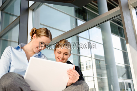 two young business woman with laptop