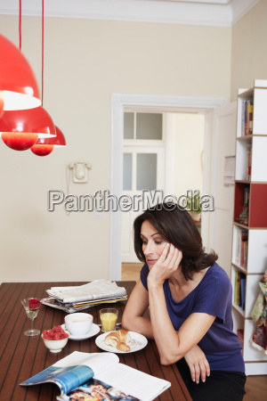 woman sitting on table reading