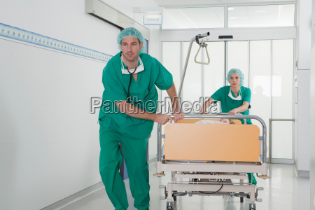 medical team in scrubs with bed
