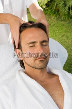 man having scalp massage outdoors