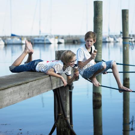 boys eating ice cream on pier
