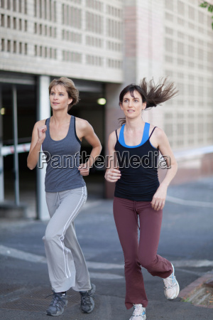 women running together on city street