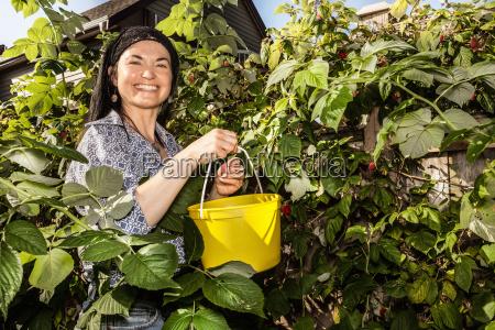smiling woman picking fruit in garden