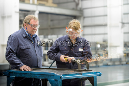 automotive apprentice and tutor using machinery