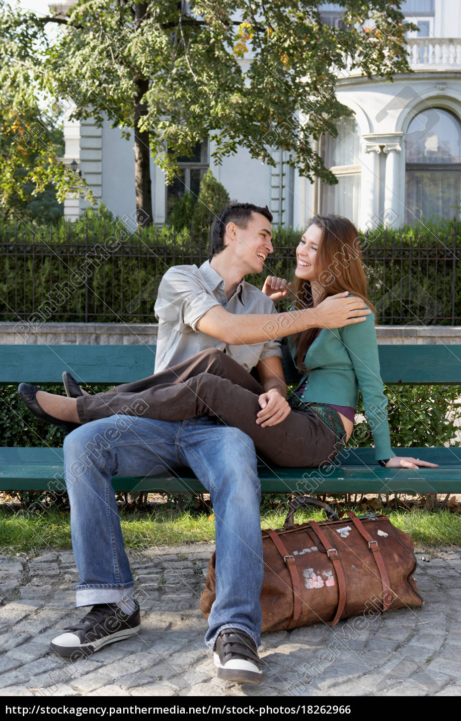couple, sitting, on, a, bench, laughing - 18262966