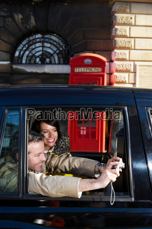 couple taking snap from taxi window