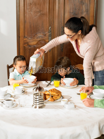 mother pouring cereal for boy