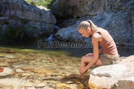 young woman sitting on rock and