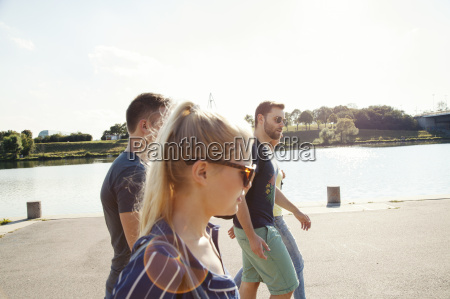 four young friends walking along riverside