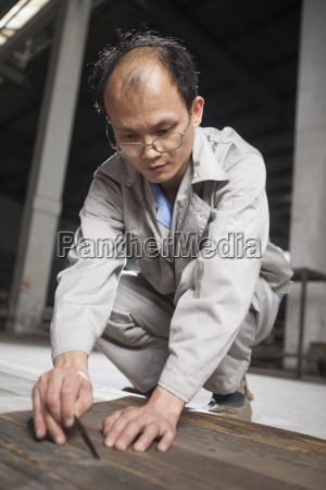 carpenter checking quality of wood plank