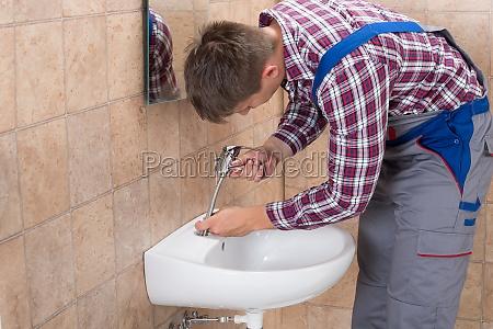 plumber fixing tap of sink