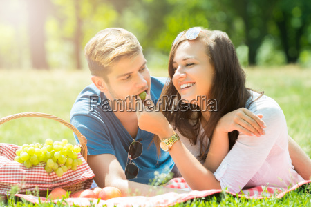 smiling woman feeding grape to her