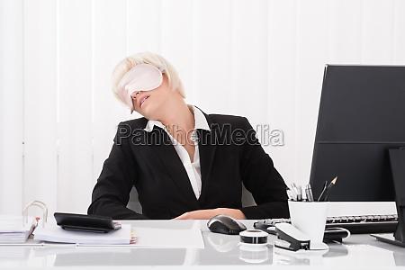 businesswoman wearing eye mask and sleeping