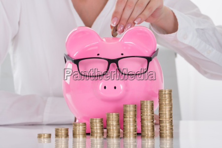 females hand inserting coin in piggybank