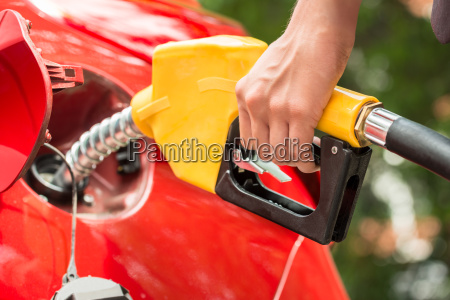 businesswomans hand refueling cars tank