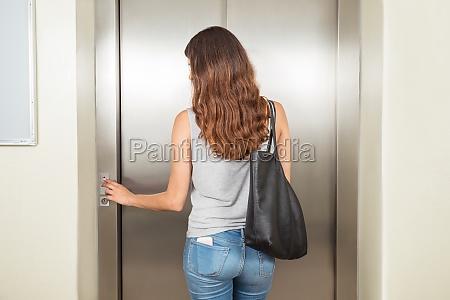 woman with handbag using elevator
