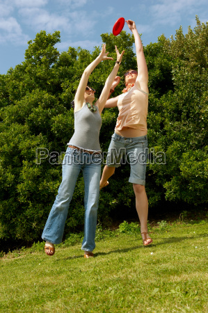 two women jumping to catch a