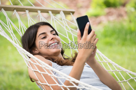 woman relaxing in hammock using mobile