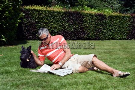 mature man laying on grass reading