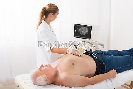 doctor using ultrasound scan on abdomen
