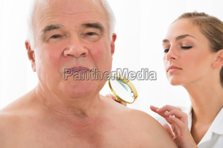 doctor examining skin of patient with