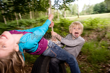 boy and girl on tire swing
