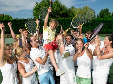people raising the winner tennis court