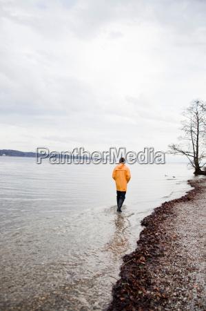 man in raincoat wading along shore