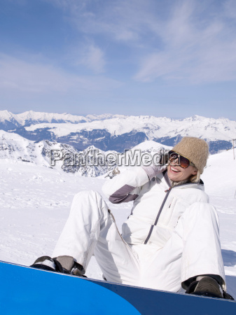 woman sitting in the snow using