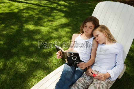 girls reading book together